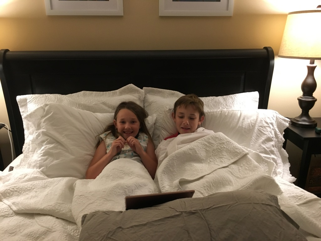 Grandchildren snuggled in bed.